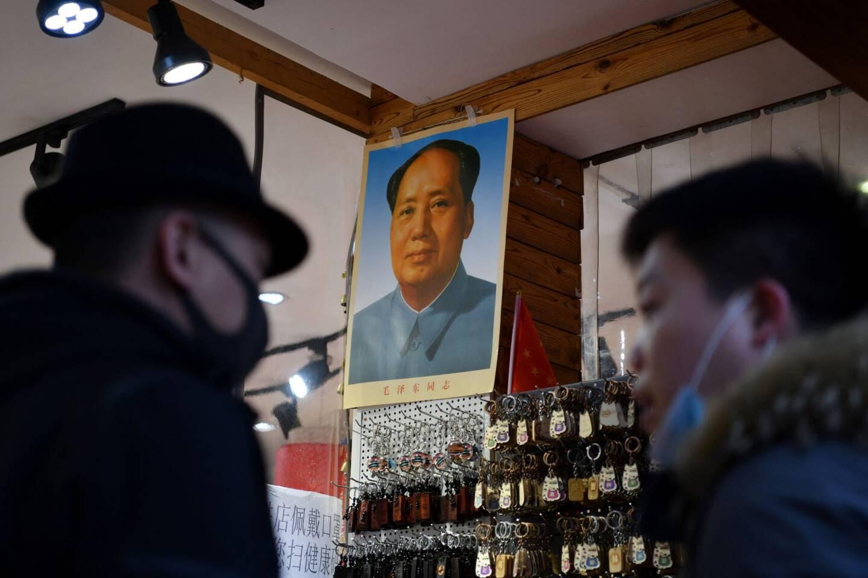 Deux hommes devant le portrait de Mao Zedong en Chine.