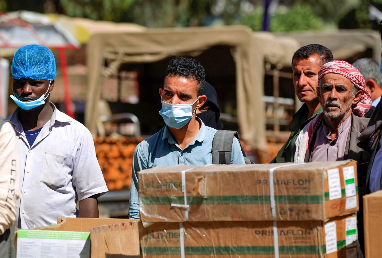 Des hommes attendent la distribution de nourriture devant un hôpital dans la capitale du Yémen, Sanaa.