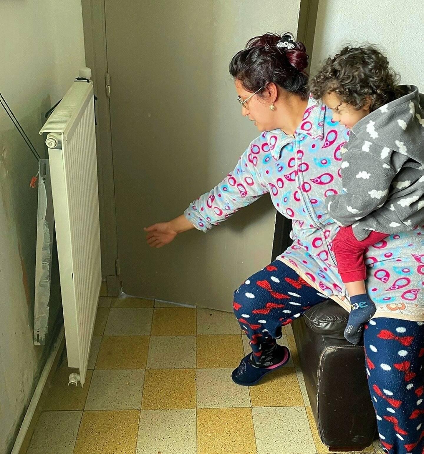 Une locataire montre le radiateur descellé dans un appartement où vivent des enfants.