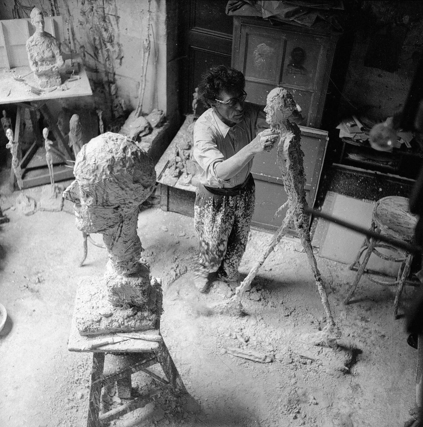 Alberto Giacometti travaillant au plâtre de l'Homme qui marche dans l'atelier, 1959.