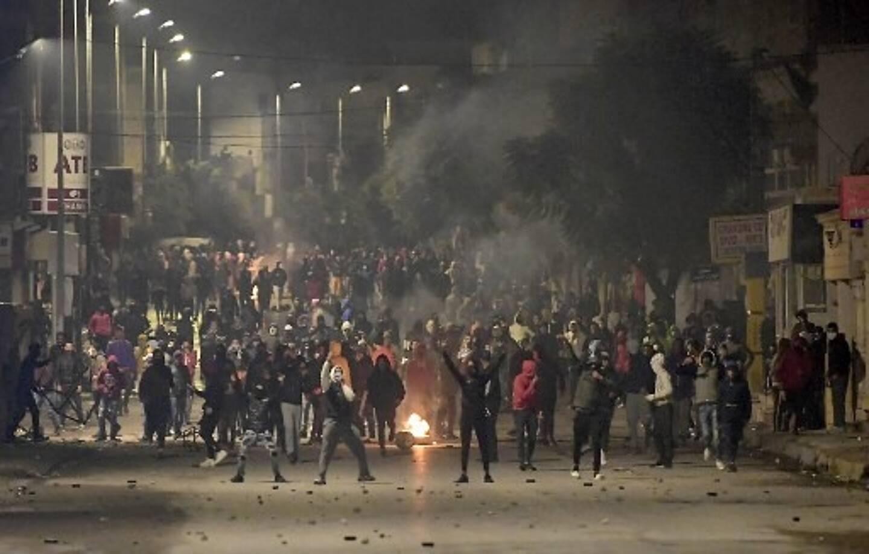Les manifestants se tiennent au milieu des fumées alors qu'ils bloquent une rue lors d'affrontements avec les forces de sécurité dans la banlieue d'Ettadhamen, dans la banlieue nord-ouest de Tunis, la capitale tunisienne, le 18 janvier 2021, au milieu d'une vague de manifestations nocturnes dans ce pays d'Afrique du Nord.