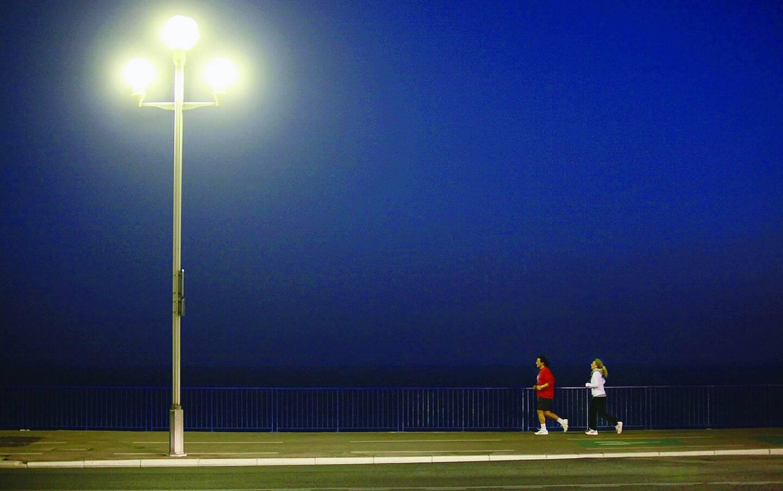 Des coureurs sur la Promenade des Anglais, à Nice, la nuit tombée