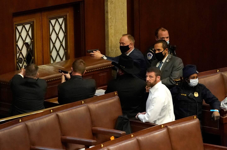 Les agents de la police du Capitole à Washington D.C. pointent leurs armes vers la porte attaquée par les supporters du président Donald Trump entrés par effraction dans la House Chamber ce mercredi.