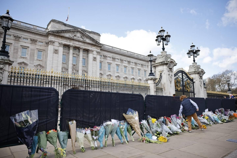 Des fleurs sont déposés le long de la grille du palais de Buckingham, le 11 avril 2021 deux jours après l'annonce du décès du prince Philip