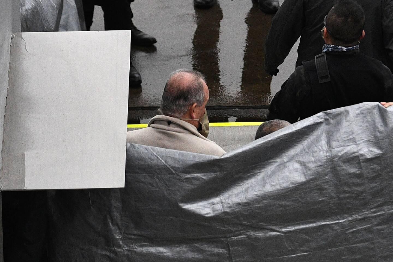 Un homme, supposé être Michael Taylor, accusé d'avoir aidé Carlos Ghosn dans sa fuite, est escorté par des policiers japonais à son arrivée à l'aéroport de Narita, le 2 mars 2021