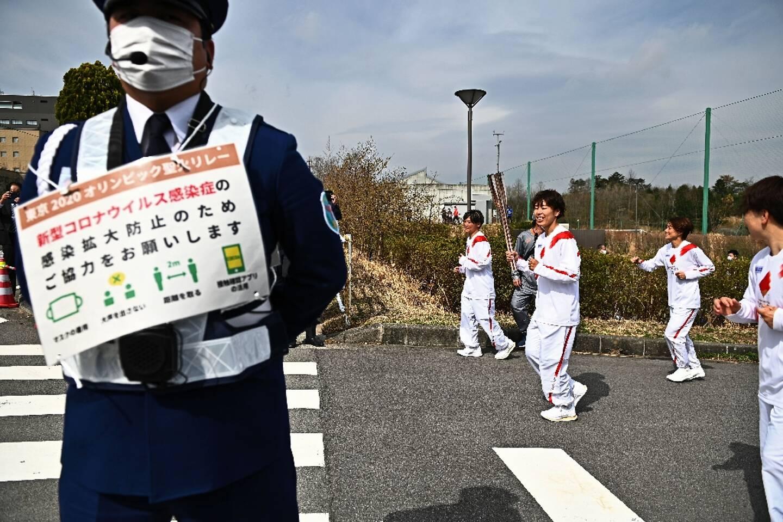 La footballeuse internationale japonaise Azusa Iwashimizu porte la torche habritant la flamme olympique à Naraha dans le département de Fukushima le 25 mars 2021.