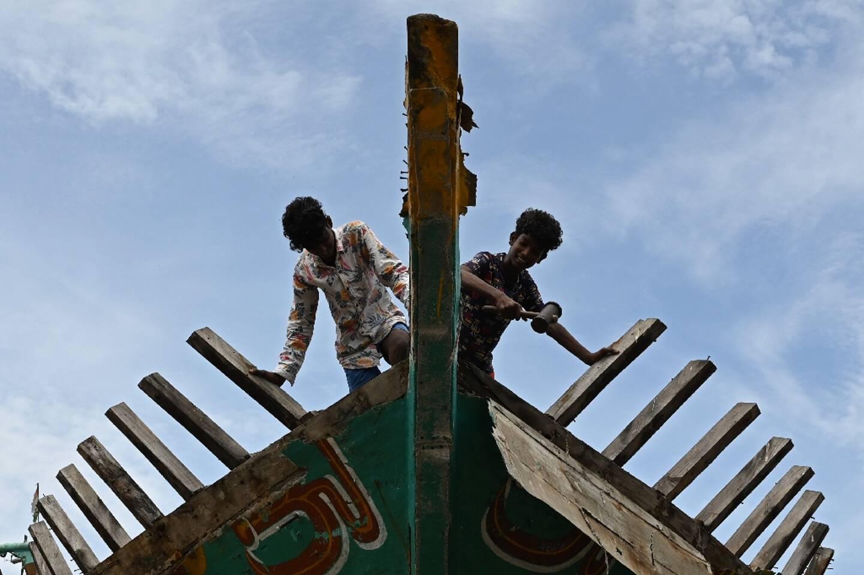 Des ouvriers font des travaux de maintenance sur un bateau de pêche dans le port de Kasimedu, après l'allègement des restrictions contre le  Covid-19 à Chennai, en Inde, le 10 juin 2021