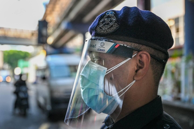 Un policier porte une double protection sur le visage à Kuala Lumpur le 1er juin 2021