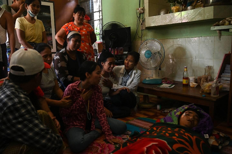 La famille du protestataire birman Chit Min Thu, tué d'une balle dans la tête par les forces de sécurité lors d'une manifestation, est rassemblé autour de son corps, le 11 mars 2021 à Rangoun