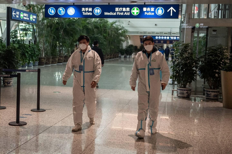 Des soignants à l'aéroport de Wuhan (Chine), avant l'arrivée d'une équipe de l'OMS, le 14 janvier 2021