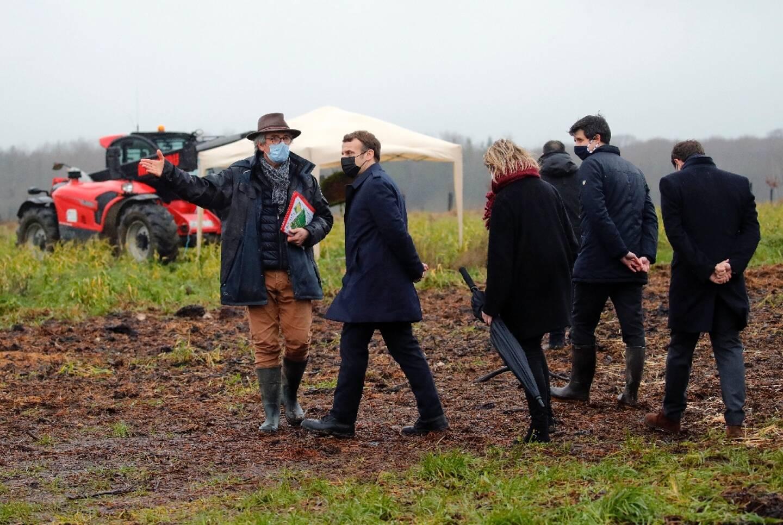 Le président français Emmanuel Macron, avec le ministre de l'Agriculture Julien Denormadie, en visite dans la ferme des Ruelles, de Michel Galmel (gauche), le 12 janvier, à Tilly en Normandie