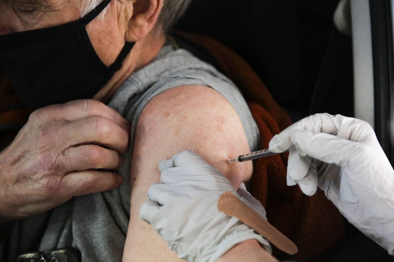 """Un habitant de Washington se fait vacciner le 26 janvier contre le Covid-19 au volant de sa voiture, dans l'un des quatre centres de vaccination """"drive in"""" ouverts localement."""