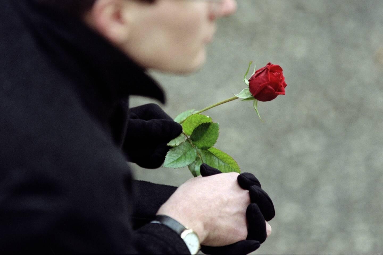 Un homme tient une rose devant l'église de Jarnac lors des funérailles de l'ancien président François Mitterrand, le 11 janvier 1996