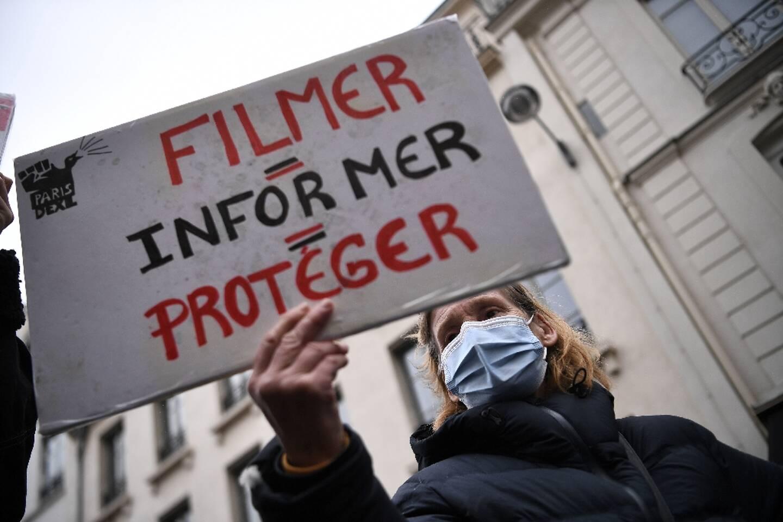 """Une manifestante tient une pancarte """"filmer = informer = protéger"""" durant une manifestation contre la loi sécurité globale devant le Sénat le 16 mars 2021"""