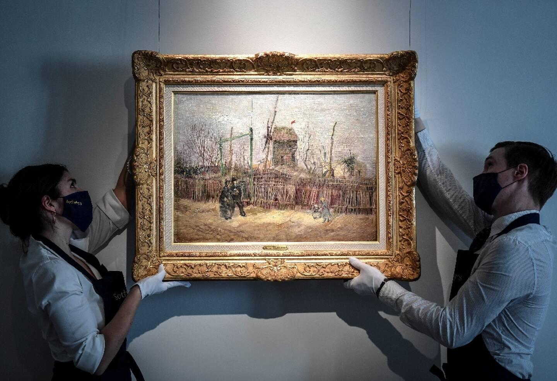 """Des employés mettent en place l'oeuvre du peintre néerlandais Vincent Van Gogh """"Scène de rue à Montmartre"""" (1887) au sein de la maison d'enchères Sotheby's à Paris le 24 février 2021"""