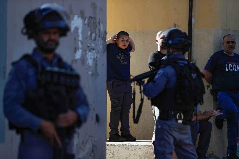 Un jeune Palestinien regarde des soldats israéliens déployés lors d'une manifestation à Jaffa (Israël), le 15 mai 2021