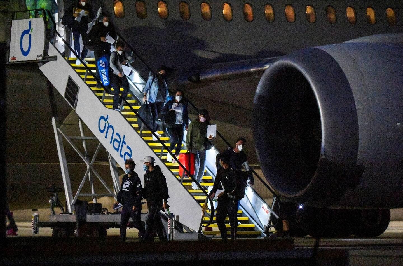 Joueurs de tennis et officiels descendent de leur avion à l'aéroport de Melbourne, le 14 janvier 2021