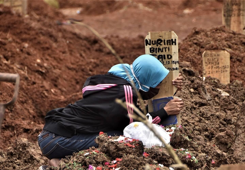 Une femme se recueille sur la tombe d'un proche décédé du Covid-19 dans un cimetière de Bekasi (Indonésie) le 28 janvier 2021.