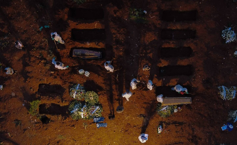 Des employés en tenue de protection enterrent des victimes du Covid-19, le 17 avril 2021 à Sao Paulo, au Brésil