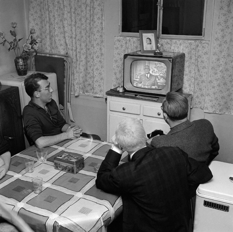 """Des Parisiens, le 23 avril 1961, écoutent l'allocution radio-télévisée du général Charles de Gaulle condamnant le putsch à Alger d'""""un quarteron de généraux en retraite"""""""