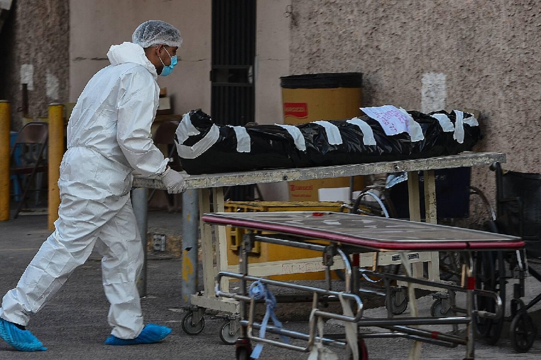 Un employé de la morgue d'un hôpital de Tegucigalpa, transporte le cadavre d'une personne décédée du Covid-19, le 27 avril 2021