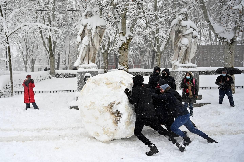 Des jeunes font une boule de neige géante à Madrid l 9 janvier 2021.