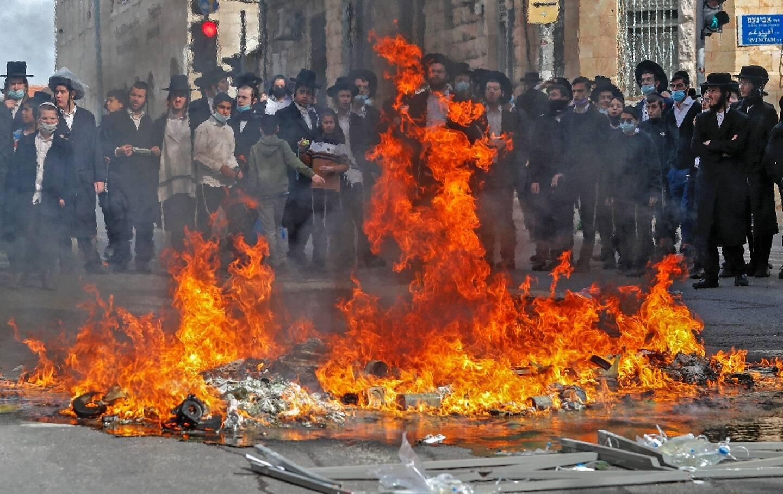 Desmanifestants ultra-orthodoxes juifs ont mis le feu à une barricade lors d'une manifestation dans le quartier de Mea Sharim, à Jerusalem, le 26 janvier 2021.