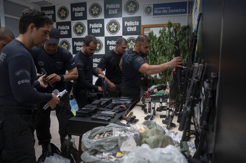 Des policiers exposent les armes et la drogue saisies  lors d'une opération antidrogue dans la favela de Jacarezinho, le 6 mai 2021 à Rio de Janeiro, au Brésil