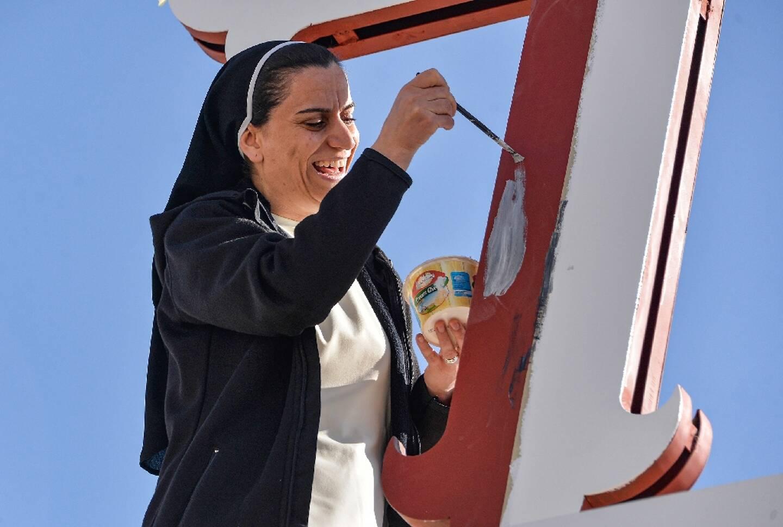 Une none décore une croix à l'entrée d'un couvent à Qaraqoch, en Irak, le 24 février 2021