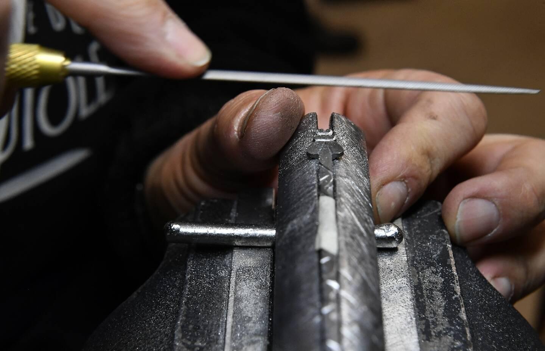 Un coutelier finalise l'abeille du ressort d'un Laguiole dans les ateliers de la Forge de Laguiole à Laguiole, dans l'Aveyron le 2 mars 2021