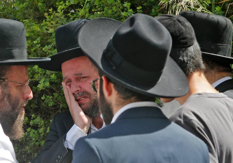 Un juif ultra-orthodoxe pleure au cimetière de Bnei Brak, près de Tel-Aviv, lors des funérailles d'une des victimes de la bousculade au mont Meron dans le nord d'Israël, le 30 avril 2021