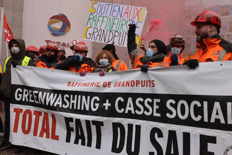 """Manifestation contre les suppressions d'emploi chez Total, accusé par ailleurs de """"greenwashing"""" par des ONG, le 9 février 2021 devant le siège du groupe, réuni en conseil d'administration, à la Défense"""