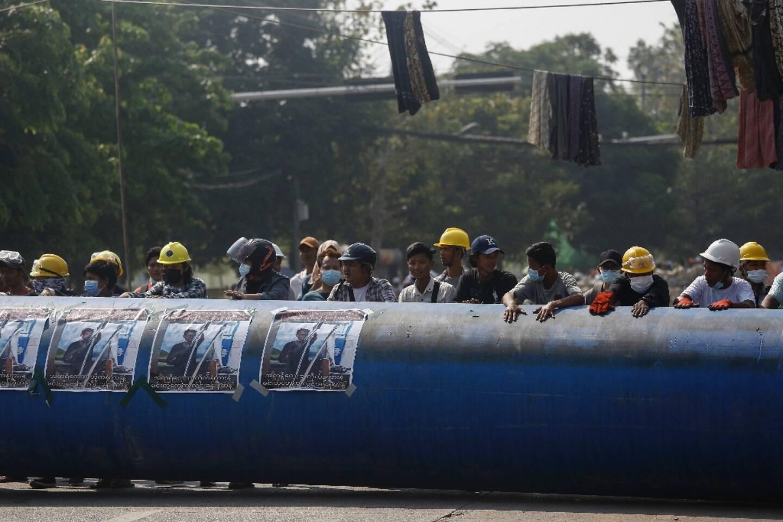 Des manifestants roulent un tuyau pour construire une barricade, à Rangoun (Birmanie) le 11 mars 2021.