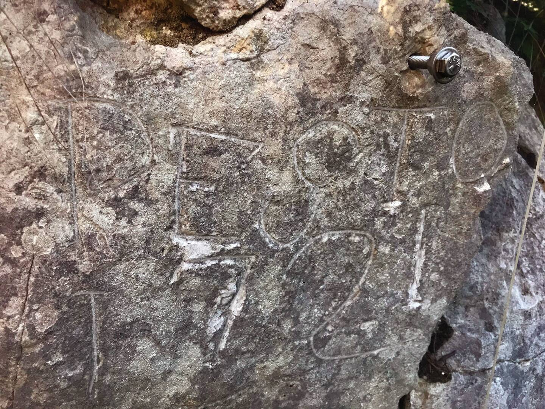 Victime de l'érosion, l'inscription, difficilement lisible, est désormais protégée par une plaque de plexiglas.