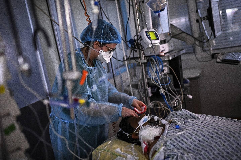 Une infirmière soigne un patient atteint du Covid-19, à l'hôpital Cochin de l'AP-HP à Paris, le 18 mars 2021
