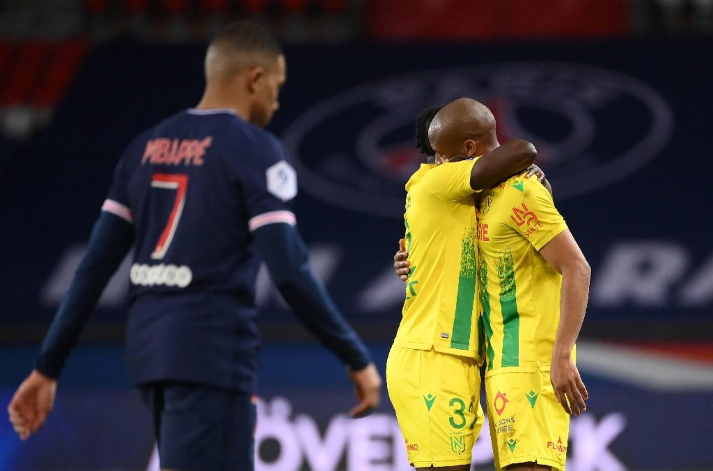 Deux joueurs nantais se congratulent après la victoire, 2 buts à 1 face au Paris Saint-Germain et son attaquant Kylian Mbappé, lors de leur match de L1, le 14 mars 2021 au Parc des Princes