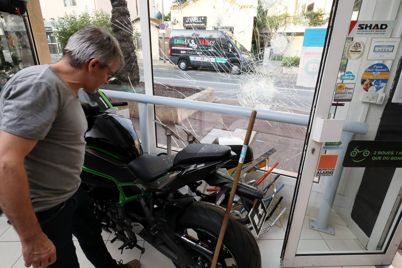 Le gérant de ce magasin de motos ne peut que constater les dégâts dans son enseigne après cette nuit de violences urbaines.