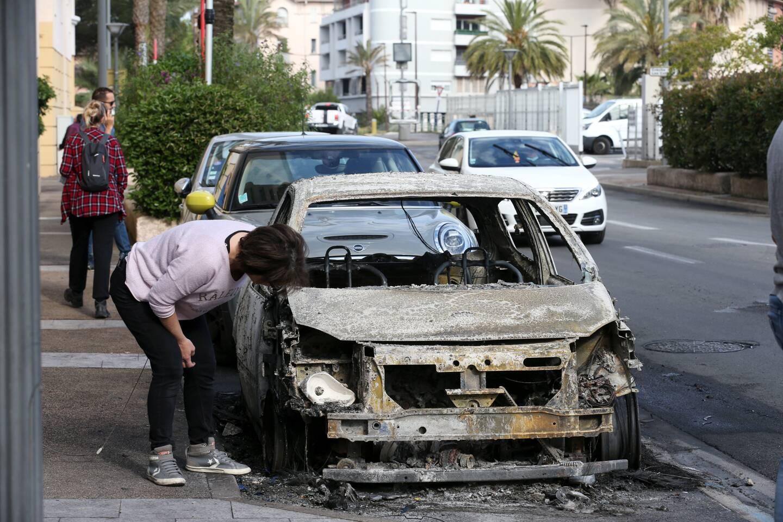 Une habitante du quartier devant la carcasse calcinée de sa voiture.
