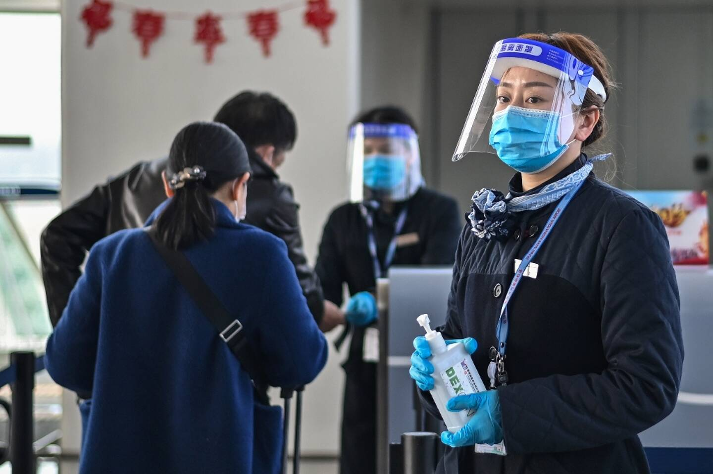 Distribution de gel hydroalcoolique à l'aéroport international de Wuhan le 12 février 2021