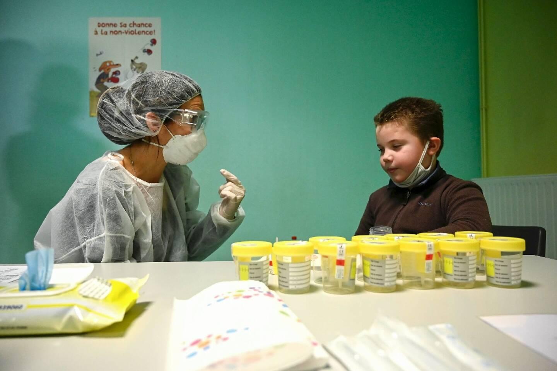 Une infirmière scolaire explique à un enfant comment il doit prélever sa salive pour faire un test dans une école de Lavoncourt (haute-Saône), le 1er mars 2021