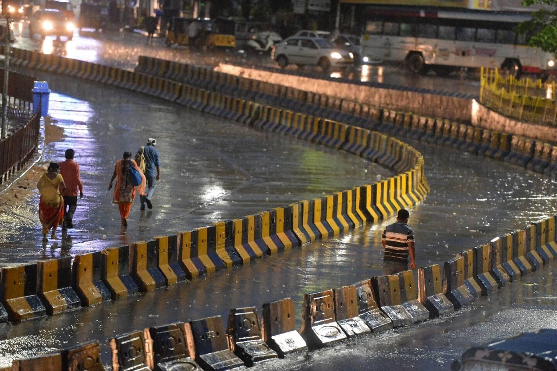 Des gens marchent sous la pluie avant l'entrée en vigueur d'un couvre-feu imposée par les autorités à Secunderabad, en Inde, pour enrayer l'épidémie de Covid-19, le 10 juin 2021