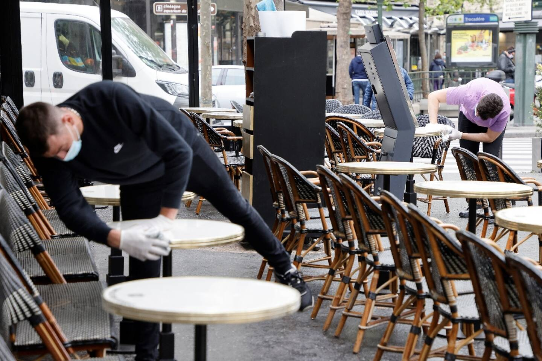 """Des employés du """"Café du Trocadéro"""" à Paris préparent la terrasse le 11 mai 2021"""