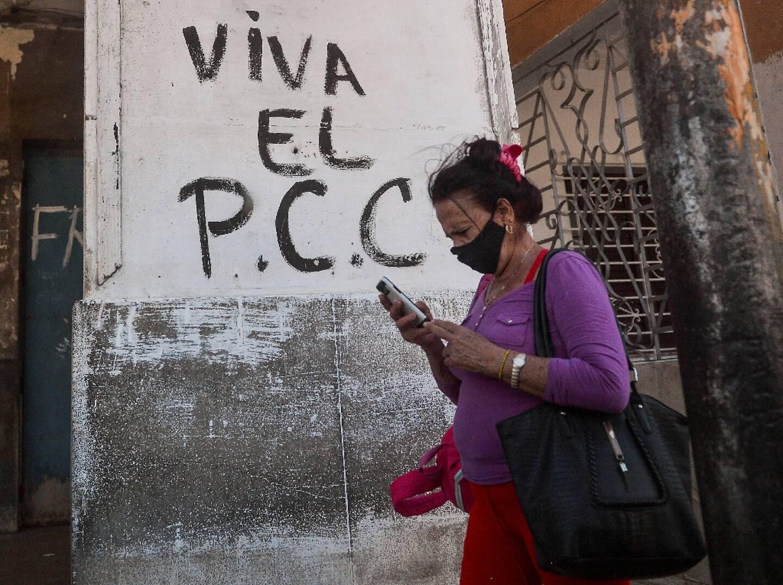 """Une Cubaine passe devant un graffiti disant """"Vive le PCC"""", le Parti communiste cubain, à La Havane le 6 avril 2021"""