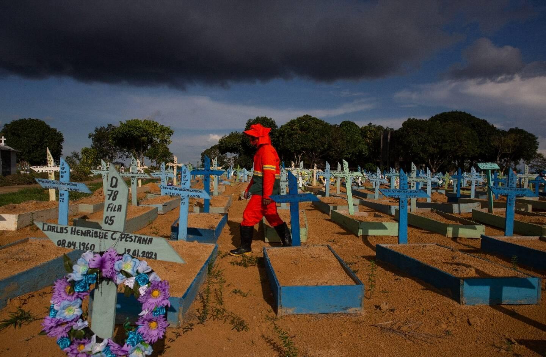 Un employé de pompes funèbres au milieu de tombes de victimes du Covid-19 dans un cimetière de Manaus (Brésil), le 29 avril 2021