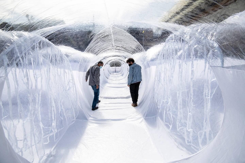 Deux hommes marchent dans un tunnel de plastique destiné à isoler les patients du covid le 16 février 2021 à Bogota