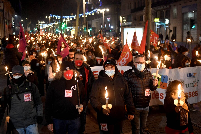 """Des manifestants bravent le couvre-feu anti-covid  et défilent au flambeau contre """"la casse sociale"""", le 12 janvier 2021 à Marseille"""