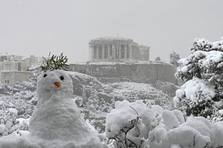 Un bonhomme de neige devant une vue du Parthénon sur l'Acropole recouverte de neige à Athènes le 16 février 2021