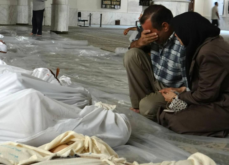 Image fournie par Shaam News Network, un média de l'opposition syrienne, montrant un couple se recueillant devant les victimes d'une attaque au gaz toxique selon l'opposition syrienne, le 21 août 2013 dans la Ghouta orientale, près de Damas