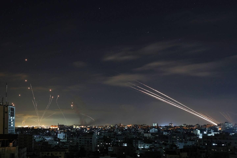 """Le bouclier antimissiles """"Dôme de Fer"""" d'Israël (g) intercepte des roquettes tirées par le Hamas depuis Gaza en direction de l'Etat hébreu, le 16 mai 2021"""