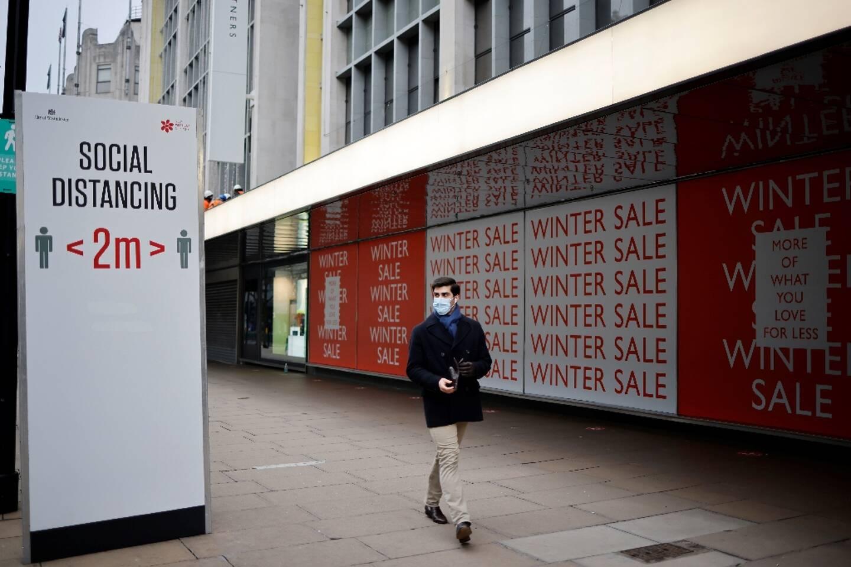 Un passant près d'un panneau incitant au respect de la distanciation sociale, le 8 janvier 2021 à Londres